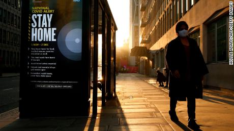 A pedestrian wearing a mask passes a digital display in London showing the new measures as England enters a second coronavirus lockdown on November 5.