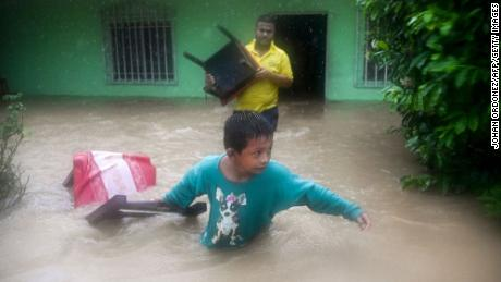 A family saves their belongings from a flooded house after heavy rains caused by Eta in Guatemala.