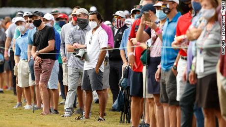 Fans, wearing masks, watch action on the ninth green during the first round of the Houston Open.