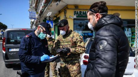 Italian Army soldiers and police carry out a document check on 23 March, 2020, in Naples, as limits are imposed on people's freedom of movement.