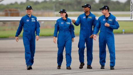 از چپ به راست ، فضانوردان Soichi Noguchi ، Shannon Walker ، Victor Glover و Michael Hopkins روز یکشنبه به سمت میکروفون در مرکز فضایی کندی حرکت می کنند.