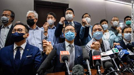 Hong Kong pro-democracy lawmakers join hands at a press conference pledging their resignation, on November 11.