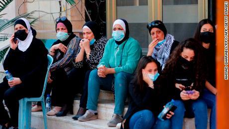 ผู้ไว้ทุกข์ชาวปาเลสไตน์สวมหน้ากากสำหรับพิธีศพของ Saeb Erekat ในเมือง Jericho เมื่อวันพุธ