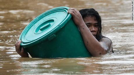 ชาวเมือง Marikina คนหนึ่งเกาะอยู่กับภาชนะพลาสติกเมื่อน้ำท่วมในพื้นที่