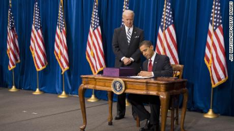 US Vice President Joe Biden stands with US President Barack Obama as he signs the American Recovery and Reinvestment Act at the Denver Museum of Nature and Science in Denver, Colorado, on February 17, 2009.