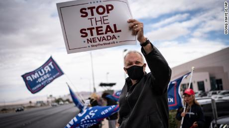 "Supporters of President Donald Trump hold ""Stop the Steal"" signs as they stand outside of the Clark County Elections Department in Nevada on November 7."