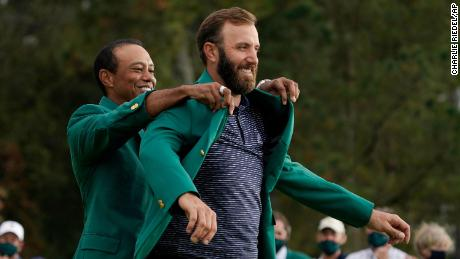 Tiger Woods helps Masters' champion Johnson with his Green Jacket.