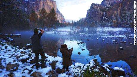 Erick Jensen (left), of Seattle, and Ruth Reyes (right), of LA, take in the Yosemite Valley November 9, following the weekend's snowstorm in Yosemite National Park, California.