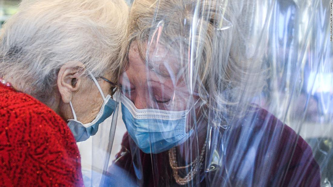 "A nursing-home resident, sinistra, speaks with her visiting daughter through a plastic screen in Castelfranco Veneto, Italia, in novembre 11. The plastic screen is part of a ""Hug Room"" that allows residents and their families to embrace each other during the coronavirus pandemic."