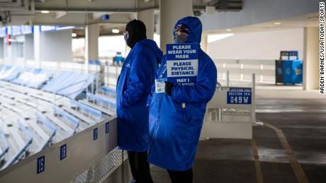 A stadium worker holds a sign reminding attendees to wear a mask and physical distance during the game between the Kentucky Wildcats and Vanderbilt Commodores at Kroger Field in Lexington, Kentucky.