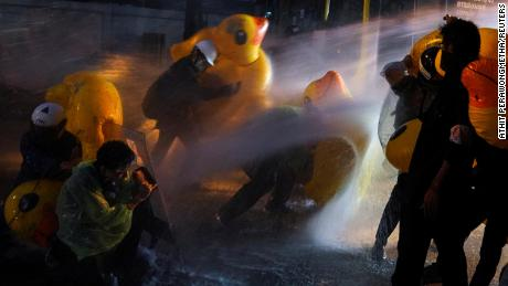 Demonstrators use inflatable rubber ducks as shields to protect themselves from water cannons during an anti-government protest outside the parliament in Bangkok, on November 17, 2020.