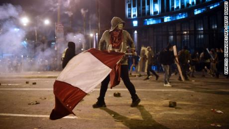A demonstrator, supporter of Peruvian ousted President Martin Vizcarra, holds a Peruvian flag during clashes on November 14, 2020.
