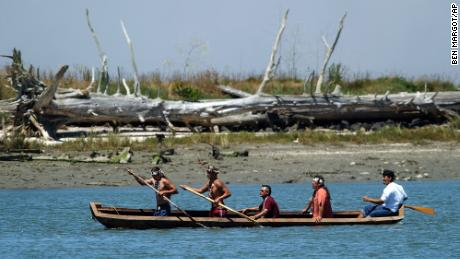 Members of the Wiyot tribe paddle a canoe from Duluwat Island across Humboldt Bay on June 25, 2004.