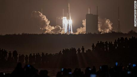 Crowds watch in the early hours of the morning as the rocket carrying Chang'e-5 launches.