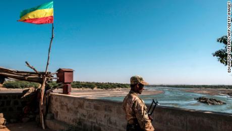 یکی از اعضای نیروهای ویژه آمهارا در 22 نوامبر در گذرگاه مرزی با اریتره که در آن پرچم امپراتوری اتیوپی موج می زند ، در هومرا ، اتیوپی تماشا می کند.