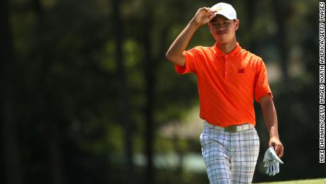Tianlang Guan walks up the 18th fairway during the second round of the Masters. Guan was given a one-shot penalty following his second shot on the 17th hole when he again exceeded the 40 second time limit.