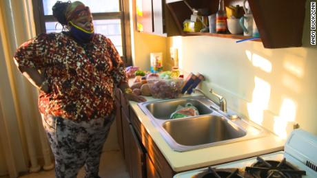 Regina Status stands in her kitchen with food from the Agatha House Foundation in the Bronx.