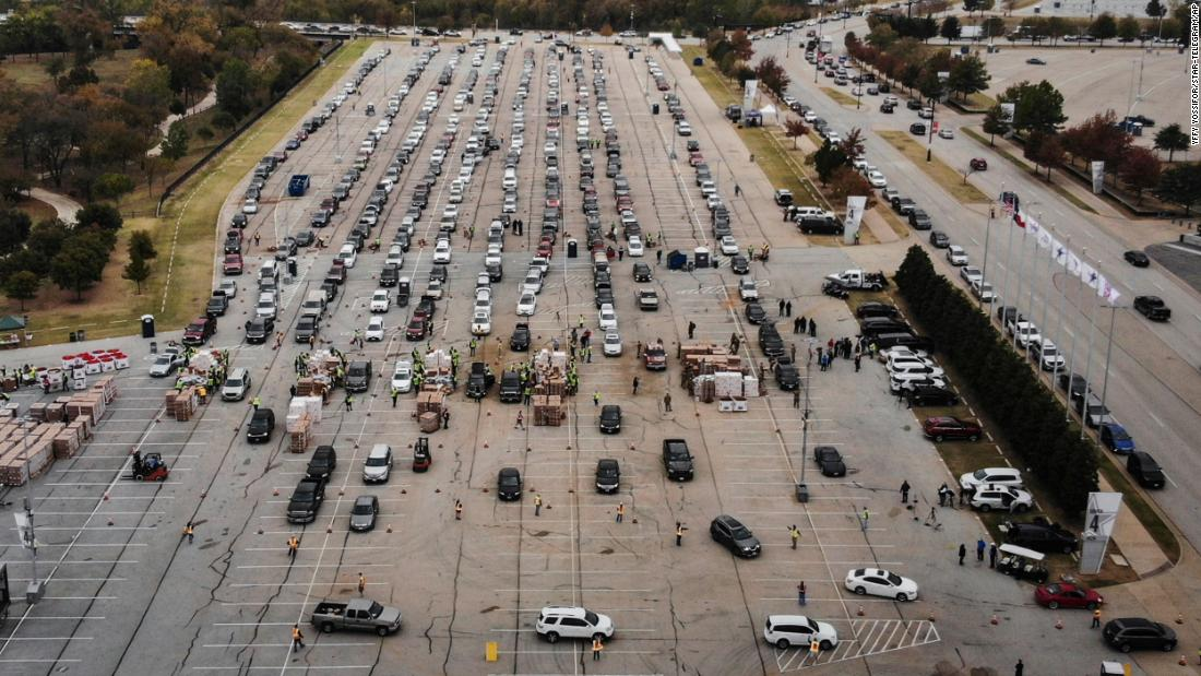 People line up in their cars to receive Thanksgiving meal boxes from the Tarrant Area Food Bank in Texas. The November 20 giveaway, the largest in the organization's history, took place in the parking lot of AT&アンプ;T Stadium in Arlington.