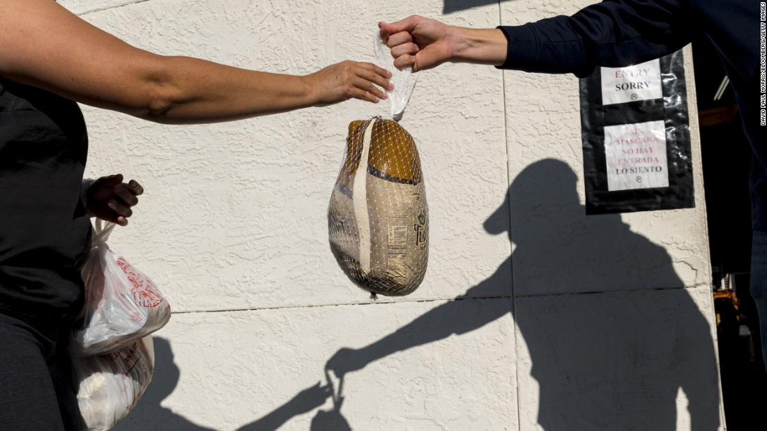 "A person hands over a turkey at the Bay Area Rescue Mission's Thanksgiving Giveaway in Richmond, カリフォルニア. The pandemic has put millions of Americans out of work, そして <a href=""http://www.cnn.com/2020/04/15/us/gallery/food-banks-coronavirus/index.html"" target=""_blank"">many families have been turning to food banks to get by.</A>"