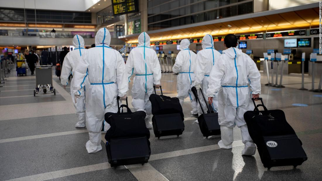 People wearing personal protective equipment walk inside Los Angeles International Airport on November 17. The airport began issuing Covid-19 tests in two terminals that week and planned to quickly expand the program.