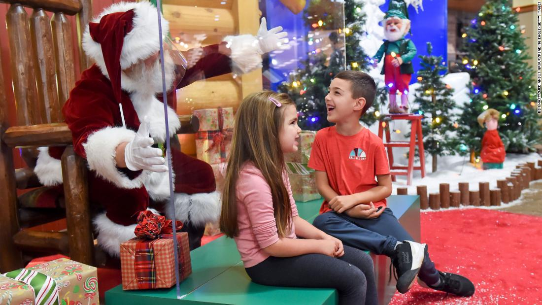 Cali Hammer and her brother Bryce take a photo with Santa, who was behind a plexiglass partition at a Cabela's store in Tilden Township, ペンシルベニア, on November 20.