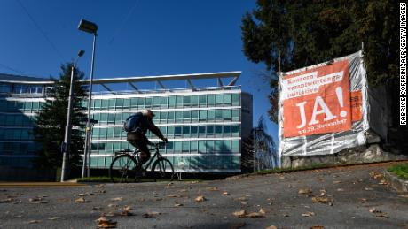 A man rides his bicycle next to the headquarters of Swiss food giant Nestlé and a campaign banner encouraging citizens to vote in favor of the Responsible Business Initiative.