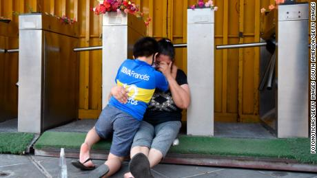 แฟน ๆ ของโบคาจูเนียร์สร้องไห้และกอดกันและกันใกล้กับ La Bombonera