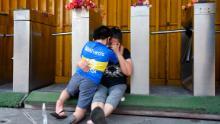 Fans of Boca Juniors cry and hug eachother near La Bombonera.