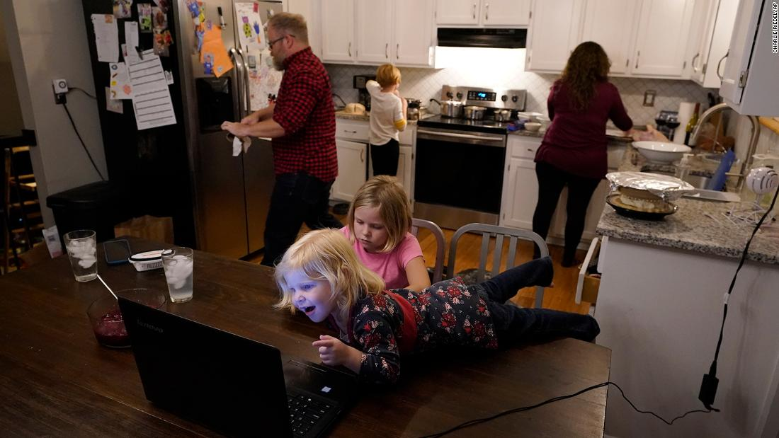 Jessica and John Franz prepare Thanksgiving dinner in Olathe, Kansas, while their daughters, Quinn and Molly, talk with family members on Thanksgiving Day.