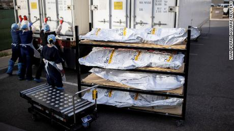 """El Paso County Medical Examiner's Office staff lock up mobile morgues before moving bodies in bags labeled """"Covid."""""""