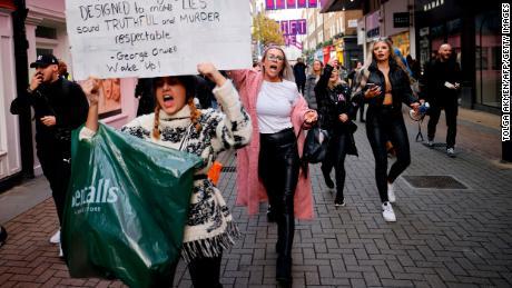 Протестующие держат плакаты, когда они принимают участие в антиблокировочной акции протеста против правительственных ограничений, призванных контролировать или смягчать распространение нового коронавируса, включая ношение масок и запирание, в Лондоне 28 ноября 2020 года.