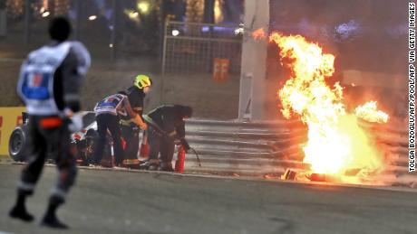 Race officials put out the fire on Grosjean's car at the Bahrain GP.