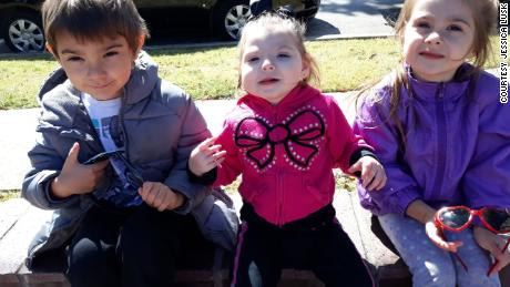 Brandi sits between Elijah and Isabella. Their parents fear it's not safe for any of them to play with friends.