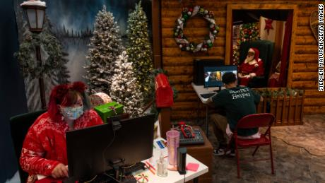 Santa Larry (R) speaks with a virtual visitor on Zoom at the Santa Experience in the Mall of America on November 24, 2020 in Bloomington, Minnesota. The owners had initially set up a socially distanced set, featuring a cabin with a plexiglass window, but moved completely online after new COVID-19 restrictions were put in place by Minnesota Gov. Tim Walz.