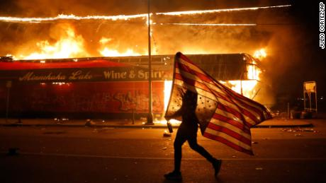 A protester carries an American flag upside down next to a burning building in Minneapolis on May 28. Protesters started rallying across the United States after the death of George Floyd, a Black man who was killed in police custody in Minneapolis.