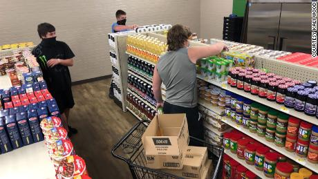 Westbrook, pictured in the grey shirt, and two of his classmates stocking the shelves at the grocery store.