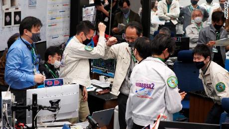Project members celebrate as the success of trajectory control maneuver by Hayabusa2 to withdraw from the Earth's sphere is confirmed.