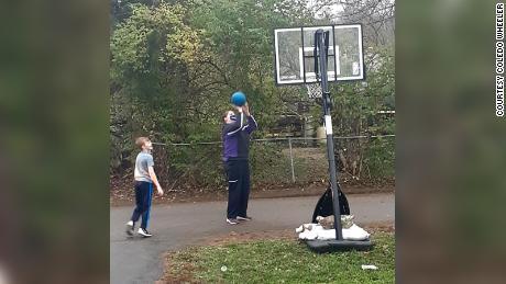 Robinson and Elijah playing basketball with his new hoop.