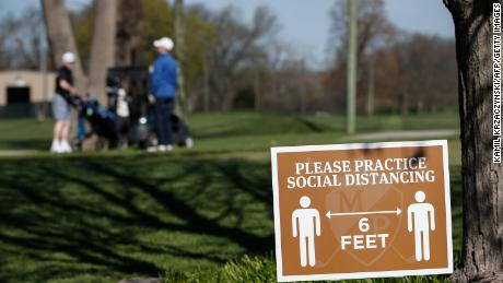 A sign informs golfers to practice social distancing at the Mt. Prospect Golf Club in Mt. Prospect, 일리노이.