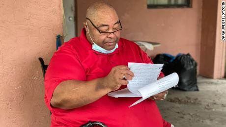 John Ayers looks through eviction documents as his eviction date looms.
