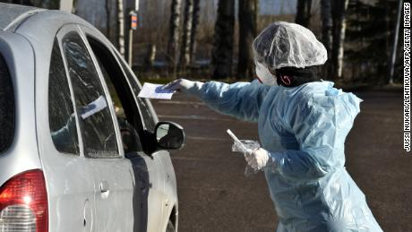 Medical workers take samples from patients at a coronavirus drive-in test center in Espoo, Finland, on April 1, 2020. (Jussi Nukari/Lehtikuva/AFP)