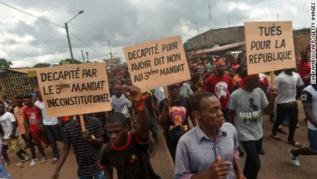 "Demonstrators hold signs reading ""Beheaded for saying no to unconstitutional third term"" and ""Killed for the republic"" during a march to denounce the death of protesters who have been killed in poll-linked violence, in central eastern Daoukro, on November 21."