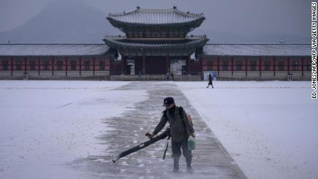A worker uses a blower to clear snow from a courtyard at Gyeongbokgung palace in central Seoul on December 13, 2020.
