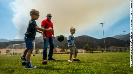 Temescal Canyon resident Gregory Tucker (中央), plays bocce ball with grandsons Mason (剩下), 5, and Griffin (对), 4, at Deleo Regional Sports Park as a smoke plume from the Holy fire blankets the sky near Corona, 加利福尼亚州, 八月 7, 2018.