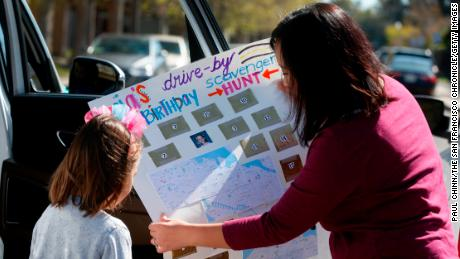 Christine Groff (对) shows the map for a drive-by scavenger hunt to her daughter Aria (剩下) on her sixth birthday in Alameda, 加利福尼亚州, 四月 1. Aria and her family drove to the homes of 16 friends with each providing the clue for their next stop on the hunt.