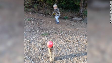 Dan DeJager, a physical education teacher in Fair Oaks, 加利福尼亚州, has created regular outdoor activities for his two sons in the pandemic. Shown is his son Henry, 3, attempting to hit a ball off a log with a Frisbee.