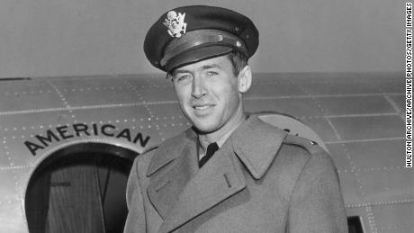 Stewart in the early 1940s with his Air Force cap in front of a military plane.