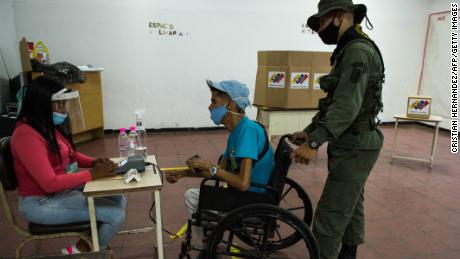 A soldier helps a man on a wheelchair as he votes at a polling station in a school in Caracas, a dicembre 6.