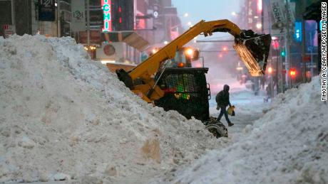 A snowplow pushes snow near Times Square on December 17, 2020 뉴욕에서, the morning after a powerful winter storm hit the US northeastern states.
