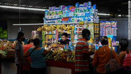 A vendor attends a stall at the municipal market of Chacao in Caracas on September 3, 2020.